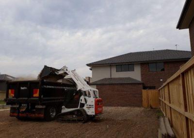 bobcat putting rubbish in bin land is cleared