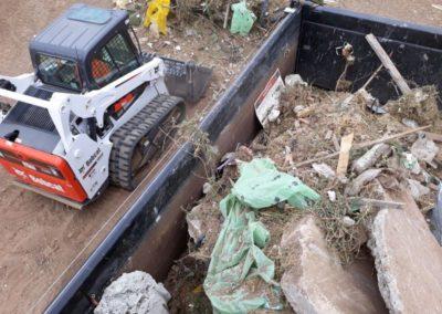 rubbish in bin bobcat on side